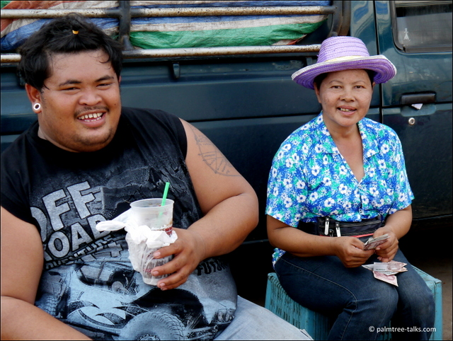 At the end of the day, the trader counts her 1,000 baht banknotes, while her worker takes a rest with icetea.